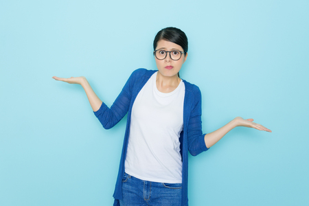 Photo for unhappy young woman showing choosing posing standing in blue wall background and looking at camera showing confused emotional face. - Royalty Free Image