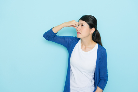Foto de beautiful young woman smelling bad odor using hands closing nose isolated on blue background. - Imagen libre de derechos