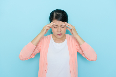 Photo pour beautiful elegant mother getting migraine problem using hands massage painful position during sick time isolated on blue background. - image libre de droit