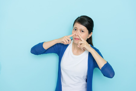 Photo pour elegant young girl using hands pressed nose looking at camera when she smelling bad taste isolated on blue wall background. - image libre de droit