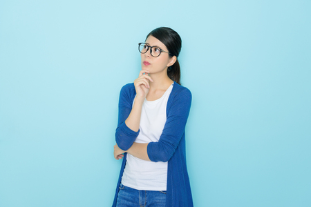 Foto de pretty elegant girl having problem feeling confused and looking at empty area thinking solution isolated on blue background. - Imagen libre de derechos