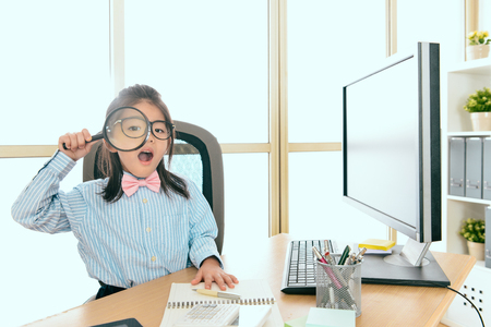 Photo pour cute beautiful little girl dressed up as business worker sitting in personal workplace and using magnifier tool looking at camera. - image libre de droit