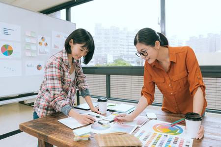 Foto de professional beauty female designer team meeting on conference desk and pointing colorful paper document to discussing choosing color. - Imagen libre de derechos