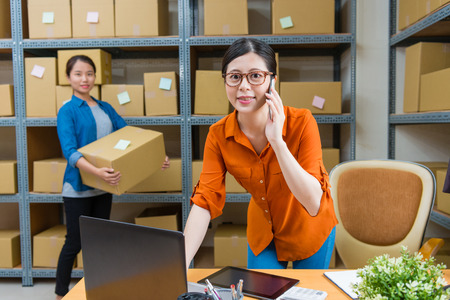 Photo for selective focus photo of smiling pretty office worker woman using mobile smartphone talking with client when her colleague holding online shopping order parcel standing in behind. - Royalty Free Image