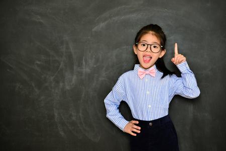 Foto de happy cheerful little girl teacher showing school education concept and standing in blackboard background having good idea. - Imagen libre de derechos