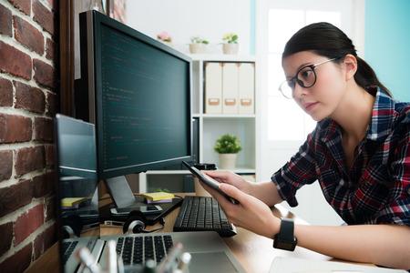 Foto de elegant attractive female programmer using mobile pad computer working and looking at laptop to think new website design idea. - Imagen libre de derechos