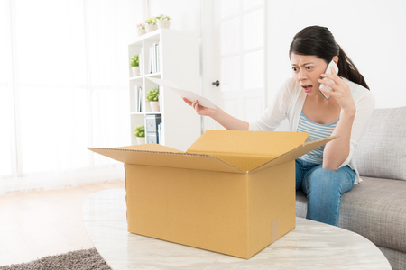 Photo for beautiful young woman received online shopping parcel opening box finding order goods is wrong feeling angry and using mobile cell phone calling for store center complaint. - Royalty Free Image