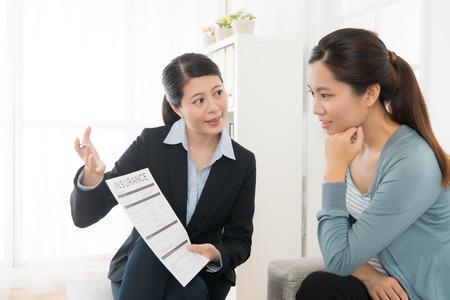 Foto de confident attractive business sales woman showing insurance case product for young girl at home and explaining scheme benefit. - Imagen libre de derechos