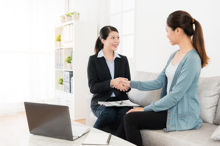Foto de happy attractive insurance agent woman with beautiful young girl sitting on sofa couch handshakes when they finished deal. - Imagen libre de derechos