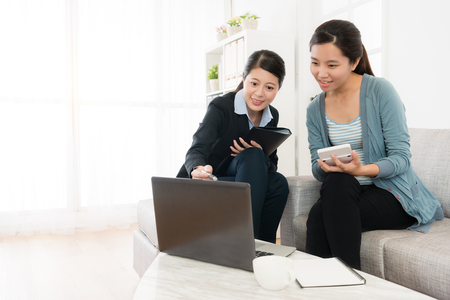 Photo pour happy smiling woman sitting on sofa couch looking at laptop and using calculator counting price when insurance advisor visiting her home. - image libre de droit