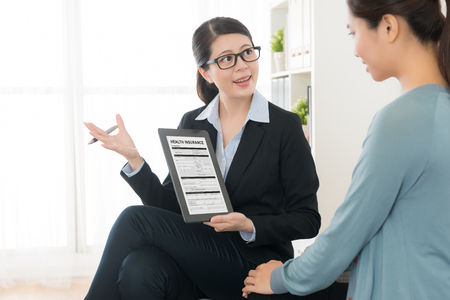 Foto de beautiful young management advisor woman using mobile pad computer showing health insurance and explaining plan to convince buyer undersigned deal. - Imagen libre de derechos