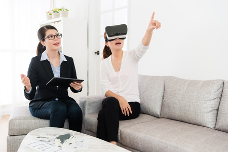 Photo pour smiling friendly house agent explaining building design when her client using VR technology equipment viewing construction and pointing imitation image asking question. - image libre de droit