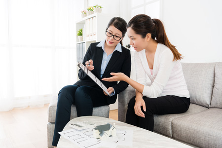Photo pour house sales manager showing deal contract document and young beauty girl asking problem to discussing best scheme for house plan. - image libre de droit