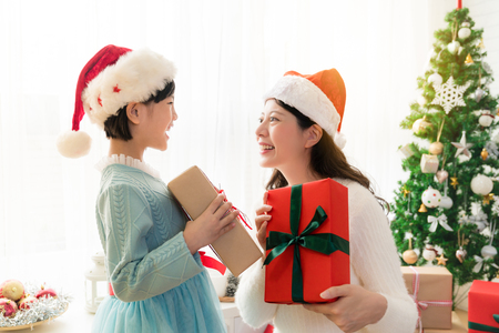 Foto de Cheerful Asian mom and her cute daughter girl exchanging gifts besides window. Parent and little child having fun near Christmas tree indoors. Morning Xmas. Portrait family close up. - Imagen libre de derechos