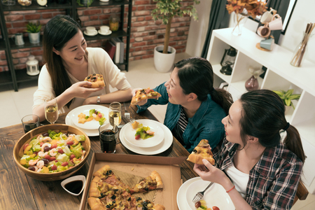 Photo pour top view of the group of people enjoys pizza together at home. - image libre de droit