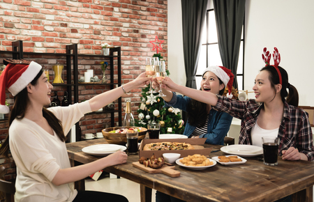 Photo for three Asia young girl friends holding the glass of champagne celebrating Christmas at home - Royalty Free Image