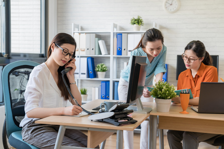 Photo for Beautiful young manager talking on the phone for a new project while two colleagues discuss in the background. - Royalty Free Image