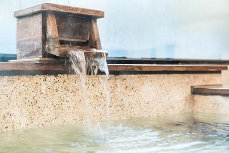 Foto de hot spring water come out from bathtub and fill in to the bath. - Imagen libre de derechos