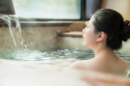 Photo for rear side view of charming girl stay in hot spring water and enjoy the view - Royalty Free Image