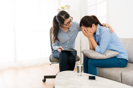 Foto de beautiful pretty girl sitting on sofa crying when she talking with doctor and psychologist comforting her in clinic office. - Imagen libre de derechos