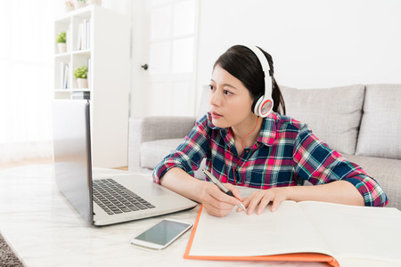 Foto de Pretty beautiful female student wearing headset sitting in living room and using mobile laptop through e-learning system studying. - Imagen libre de derechos