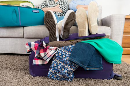Foto de closeup of two people put legs on luggage suitcase with many messy clothing and sitting on sofa couch talking discussing travel plan. - Imagen libre de derechos
