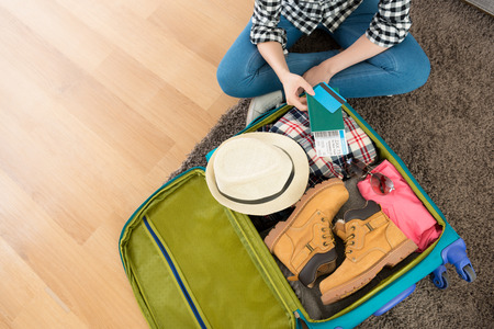 Photo pour high angle view photo of young woman sitting on living room floor packing luggage showing boarding card and passport with credit card. - image libre de droit