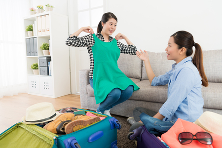 Foto de happy smiling woman showing clothing dress for friend and discussing travel planning in living room when they packing luggage at home. - Imagen libre de derechos
