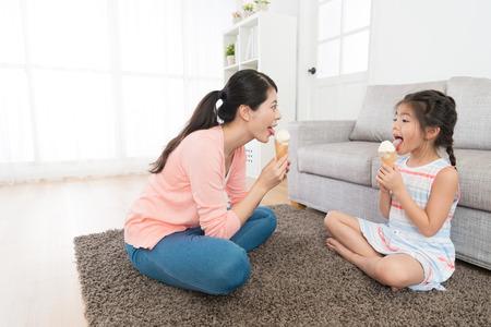 Foto de happy pretty mother sitting on living room floor with lovely beauty daughter licking ice cream enjoying summer season at home. - Imagen libre de derechos