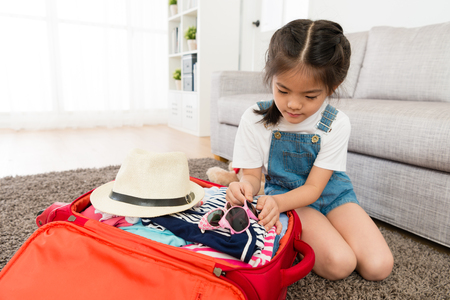 Foto de beautiful young little girl put sunglasses in travel luggage suitcase when she preparing go to trip with family during summer vacation. - Imagen libre de derechos
