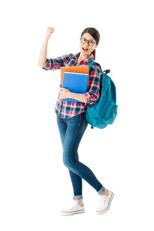 Foto de beautiful sweet school girl showing cheer up gesture looking at camera and carrying studying bag with textbook isolated on white background. - Imagen libre de derechos
