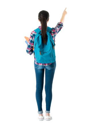 Foto de back view photo of pretty elegant girl college student pointing empty area standing on white background. - Imagen libre de derechos