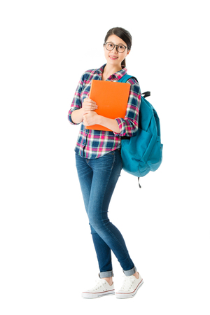 Foto de smiling attractive student holding education textbook standing on white background. - Imagen libre de derechos
