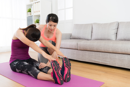 Foto de young beautiful female student stretching body and using hands touching legs training with her home fitness teacher in living room. - Imagen libre de derechos