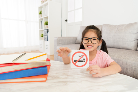 Photo pour smiling lovely little girl looking at camera presenting no smoking notice. - image libre de droit