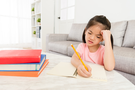 Foto de sad unhappy little female children writing english homework before back to school feeling difficulty and upset. - Imagen libre de derechos