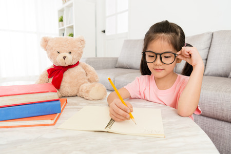 Photo pour smiling beauty female kid student studying at home with teddy bear and writing school homework preparing back to school. - image libre de droit