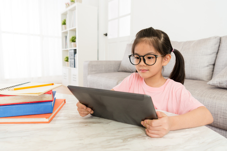 Photo pour attractive young female kid children sitting in living room at home and using mobile digital tablet watching online video. - image libre de droit