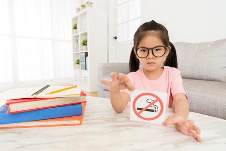 Foto de beauty elegant girl kid showing no smoking sign to camera when she doing school studying homework in living room at home. - Imagen libre de derechos