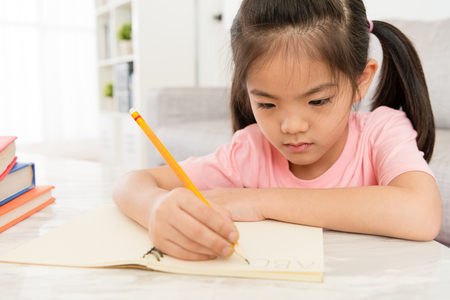 Photo pour closeup photo of pretty attractive little female children doing homework at home and writing school book learning english ready back to school. - image libre de droit