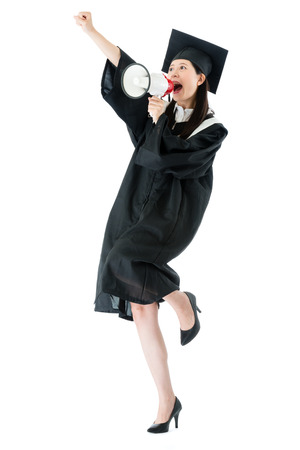 Photo pour happy beautiful female graduate finished college studying on white background and using loudly megaphone talking to cheer celebrating. - image libre de droit