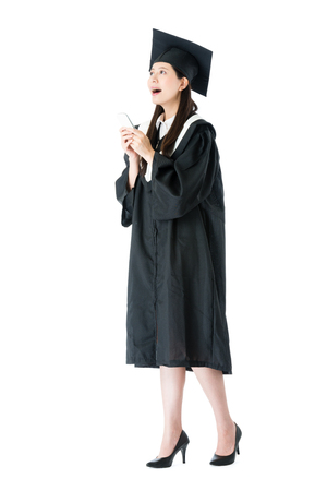 Foto de happy cheerful female university student graduate walking on white background and using mobile smartphone looking for workplace plan information. - Imagen libre de derechos