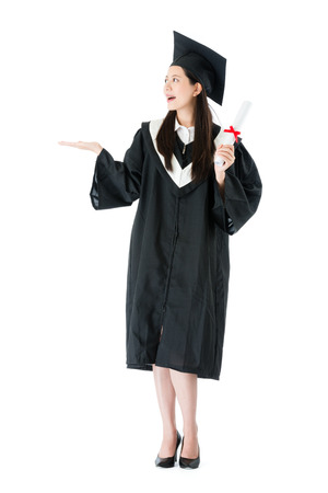 Foto de smiling elegant woman student wearing graduation clothing standing on white background and making presenting gesture showing empty area. - Imagen libre de derechos