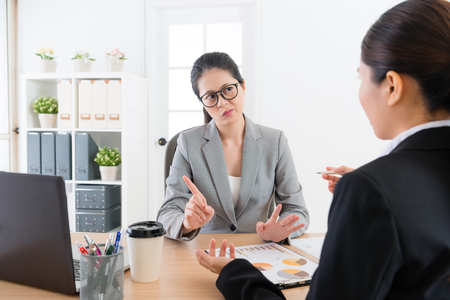 Foto de beautiful young business sales woman introducing company new product for partner but female manager feeling unsatisfied and refusing signing deal. - Imagen libre de derechos