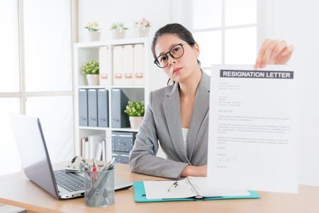Foto de professional young business woman looking at camera showing resignation letter when she decided leaving company to change new job. - Imagen libre de derechos