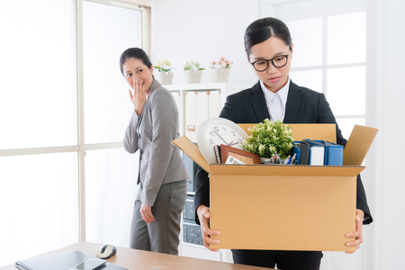 Foto de attractive beauty business girl holding personal belongings box ready to leave company and her colleague in back ridicule. - Imagen libre de derechos