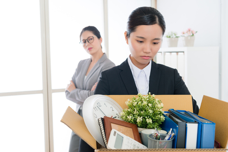 Photo pour sad pretty office worker girl losing company job packing personal items ready to leave and her manager looking at her feeling happy. selective focus photo. - image libre de droit