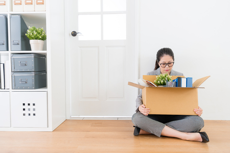 Photo pour pretty beauty female business worker is fired and holding personal items box sitting on company exit wood floor crying thinking future. - image libre de droit
