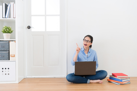 Photo for attractive woman sitting on wood floor at home using computer doing studying homework having good idea with white background. - Royalty Free Image