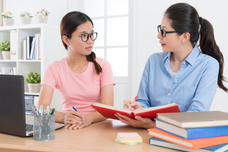 Photo for young confident education tutor woman holding textbook and explain studying content for her student. - Royalty Free Image